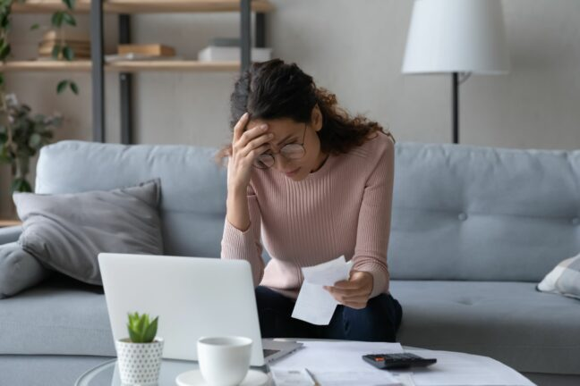 unexpected life events; worried woman reviewing bills